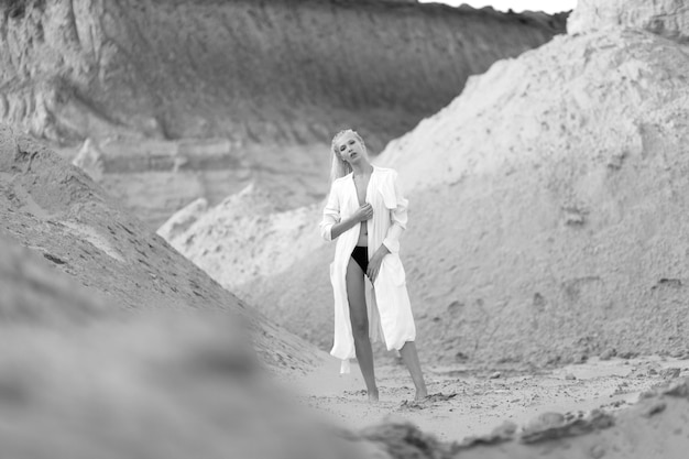 真ん中の砂の砂漠で裸足で白いロングシャツのブロンドの髪を持つ女性の白人モデルの完全な長さの肖像画。