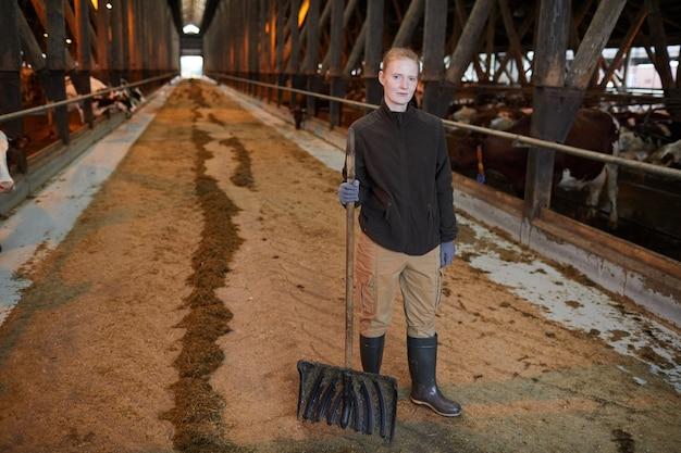 가족 목장에서 소 창고를 청소하는 동안 카메라를 찾고 여성 농장 노동자의 전체 길이 초상화, 복사 공간
