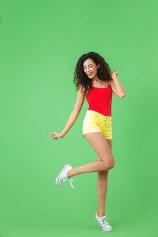 Полный портрет фитнес-девушки, одетой в летнюю одежду, улыбающуюся и идущую, изолированную над зеленой стеной