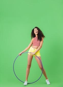 Полная длина портрет фитнес-женщины 20-х годов в летней одежде, делающей упражнения с обручем во время гимнастики на зеленой стене