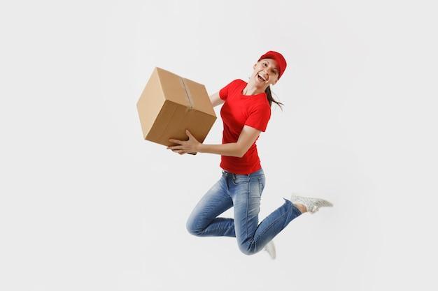 赤い帽子、白い背景で隔離のtシャツの楽しい配達の女性の完全な長さの肖像画。空の段ボール箱でジャンプする女性の宅配便またはディーラー。パッケージを受け取ります。広告用のスペースをコピーします。 Premium写真