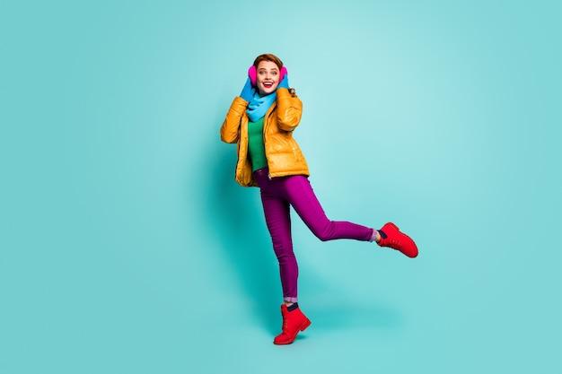 Полный портрет напуганной возбужденной женщины наслаждается осенней осенью, свободное время радуется, поднимает ноги, трогает теплый стиль, носит повседневную синюю одежду.