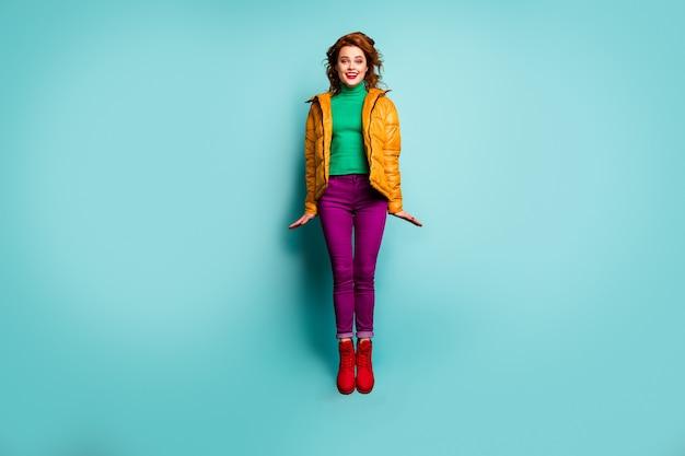 재미있는 아름 다운 아가씨의 전체 길이 초상화 점프 좋은 날씨 시즌 하루 착용 노란색 코트 자홍색 바지 녹색 터틀넥 빨간색 신발.