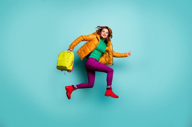 Полный портрет смешной быстрой леди прыгает в высоком темпе, уроки дома заканчиваются, несут школьную сумку, носят желтое пальто, шарф, брюки, водолазки.