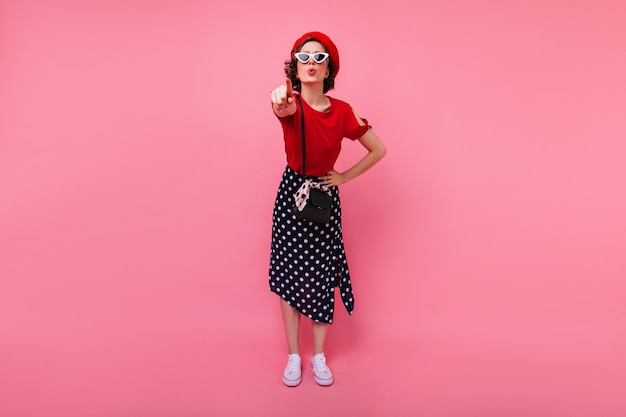 재미있는 프랑스 여자 가리키는 손가락의 전신 초상화. 분홍색 벽에 서있는 긴 치마에 웅장 한 백인 여자.