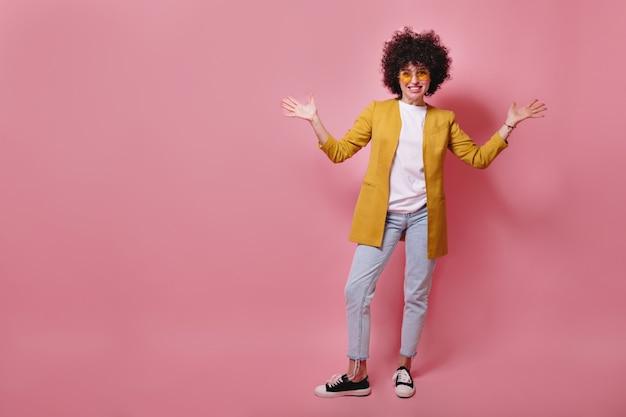 黄色のジャケットとジーンズを前に笑って短いカールを持つ面白い若い女性モデルの全身像