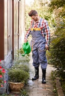 Портрет в полный рост садовника, поливающего цветок