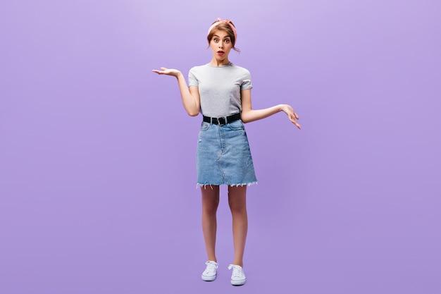 데님 스커트와 회색 셔츠에 여자의 전체 길이 초상화. 세련 된 옷과 흰색 운동 화 포즈에 분홍색 머리 띠와 놀된 여자.
