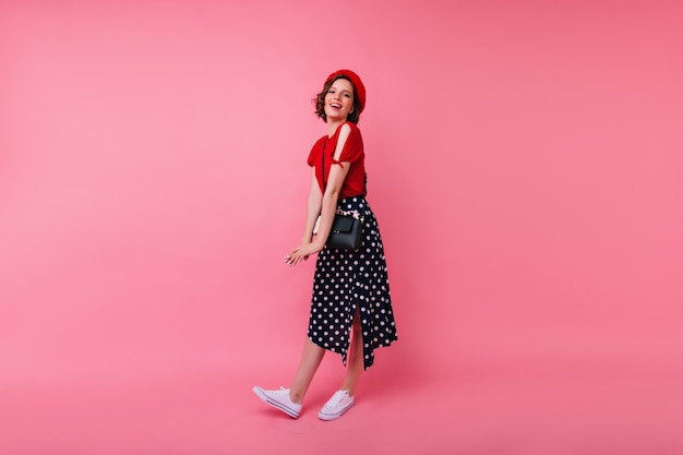 흰색 스포츠 신발에 기쁜 유럽 여자의 전신 초상화. 프랑스 빨간 베레모에 blithesome 소녀 웃음.