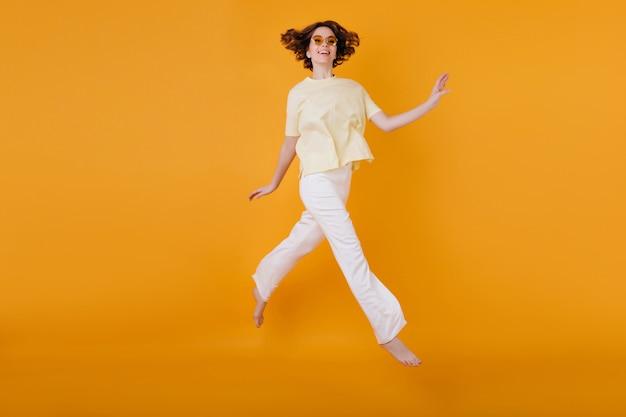 オレンジ色の壁に走っている黄色のtシャツと白いズボンの嬉しい女の子の全身像。喜んで踊る素晴らしい白人女性。