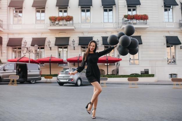 Портрет в полный рост шикарной темноволосой женщины в элегантной обуви, танцующей с воздушными шарами на улице