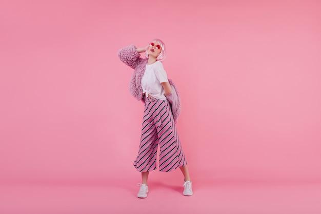 Портрет изящной кавказской дамы в полный рост в парике и белых туфлях. фото потрясающей девушки в перуке, позирующей в меховой куртке, в помещении
