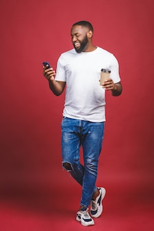 Полная длина портрет красивый афро-американский мужчина с мобильного телефона и забрать чашку кофе. изолированные на красном фоне.