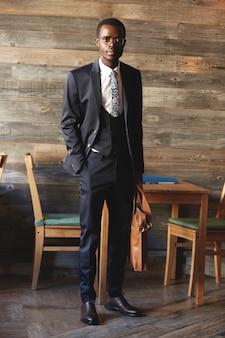 エレガントなフォーマルなスーツを着ているハンサムなアフリカの実業家の全身像》