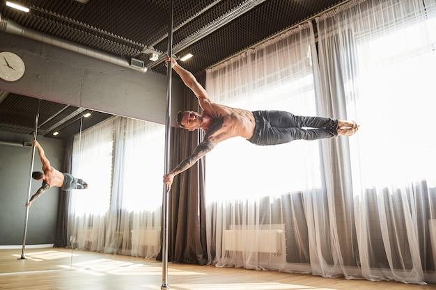 モダンダンススタジオのパイロンで回転する灰色のズボンのハンサムなひげを生やした男性の全身像