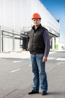 大きな倉庫に対してポーズをとるハンサムなエンジニアの全身像
