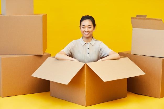 상자에 앉아 찾고 행복 아시아 여자의 전체 길이 초상화