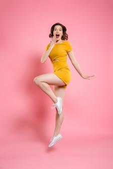 Полная длина портрет счастливой выходила красивая девушка в элегантном желтом платье, прыгая через розовый