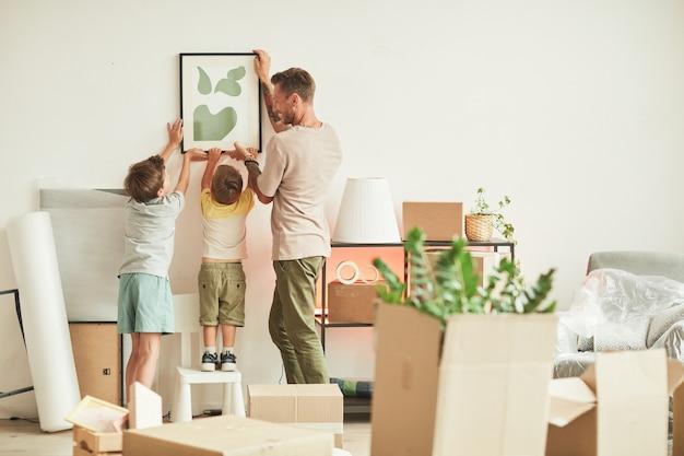 Портрет счастливого отца в полный рост с двумя сыновьями, висящими на стене картинами во время переезда в новый дом ...