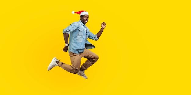 새해 산타 모자가 점프하거나 날아가는 행복한 즐거운 남자의 전체 길이 초상화, 그의 꿈을 향해 서둘러 달려가, 이빨 미소로 카메라를 바라보고 있습니다. 노란색 배경에 고립 된 실내 스튜디오 촬영