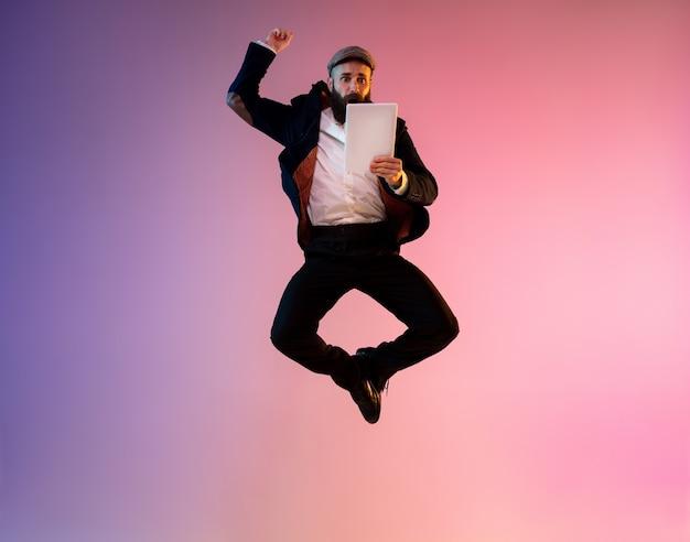 ネオンの光とグラデーションの背景で幸せなジャンプ男の完全な長さの肖像画