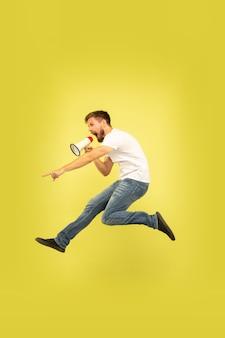 노란색 배경에 고립 행복 점프 남자의 전체 길이 초상화. 캐주얼 옷에 백인 남성 모델입니다. 선택의 자유, 영감, 인간의 감정 개념. 마우스 피스로 부르기. 무료 사진