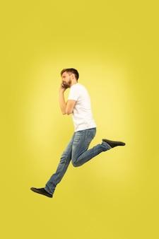 노란색 배경에 고립 행복 점프 남자의 전체 길이 초상화. 캐주얼 옷에 백인 남성 모델입니다. 선택의 자유, 영감, 인간의 감정 개념. 서둘러, 전화 통화.