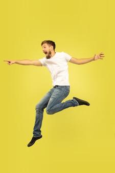 노란색 배경에 고립 행복 점프 남자의 전체 길이 초상화. 캐주얼 옷에 백인 남성 모델입니다. 선택의 자유, 영감, 인간의 감정 개념. 가리키고, 선택합니다.