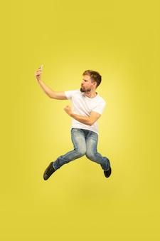 노란색 배경에 고립 행복 점프 남자의 전체 길이 초상화. 캐주얼 옷에 백인 남성 모델입니다. 선택의 자유, 영감, 인간의 감정 개념. 달리면서 셀카를 찍습니다.
