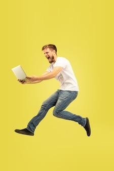 노란색 배경에 고립 행복 점프 남자의 전체 길이 초상화. 캐주얼 옷에 백인 남성 모델입니다. 선택의 자유, 영감, 인간의 감정 개념. 비행 중에 태블릿을 사용합니다.