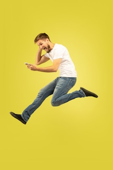 노란색 배경에 고립 행복 점프 남자의 전체 길이 초상화. 캐주얼 옷에 백인 남성 모델입니다. 선택의 자유, 영감, 인간의 감정 개념. 스포츠 베팅에서 승리.