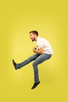 黄色の背景に分離された幸せなジャンプ男の全身像。カジュアルな服装の白人男性モデル