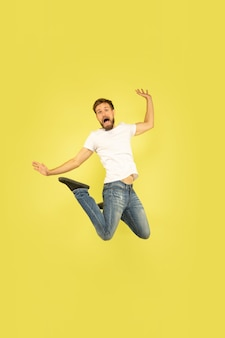 黄色に分離された幸せなジャンプの男の全身像