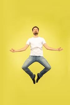 Полный портрет счастливого прыгающего человека, изолированного на желтом
