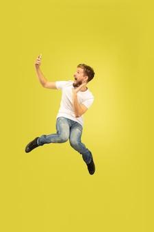 노란색에 고립 된 행복 점프 남자의 전체 길이 초상화