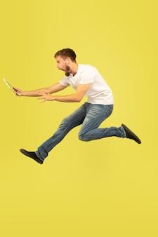 노란색 배경에 행복 점프 남자의 전체 길이 초상화