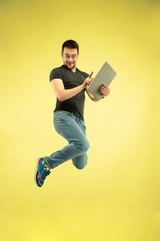 노란색 배경에 고립 된 가제트와 함께 행복 점프 남자의 전체 길이 초상화. 현대 기술, 선택의 자유 개념, 감정 개념. 비행 중 업무와 재미를 위해 노트북을 사용합니다.