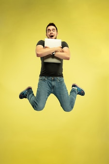 黄色で隔離のガジェットを持つ幸せなジャンプの男の完全な長さの肖像画。