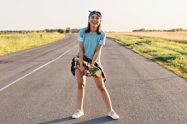 Полный портрет счастливой смеющейся женщины в повседневной футболке, короткометражке и повязке для волос, держащей в руках скейтборд и смотрящей в камеру, здоровый образ жизни.