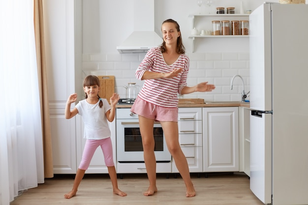 사랑하는 딸과 함께 멋진 춤을 추고, 카메라를 보고, 낙관적인 감정을 표현하고, 함께 즐거운 시간을 보내는 행복한 어머니의 전체 길이 초상화.