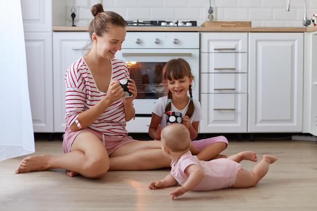 Полный портрет счастливой матери в повседневной полосатой рубашке, сидящей на полу и пьющей горячий кофе или чай, проводя время со своими дочерьми, позирующими рядом с женщиной.