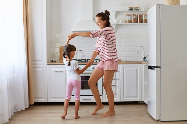 행복한 낙천적인 어머니와 딸이 집에 있는 부엌에서 함께 춤을 추고 캐주얼하게 입고 행복하고 어린 시절을 표현하는 전체 길이 초상화.