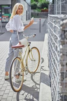 노란색 복고풍 자전거가 도시를 걷고 있는 행복한 미소 짓는 금발 여성의 전체 길이 초상화