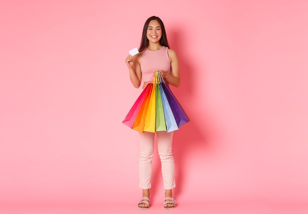 ピンクの壁の上に立って彼女の割引クレジットカードを示し、買い物袋を保持している、新しい服にお金を使うことを楽しんで幸せなトレンディなアジアの女の子の完全な長さの肖像画。