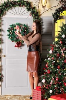 お祝いの木の近くで手にクリスマスの装飾と幸せな女性の完全な長さの肖像画