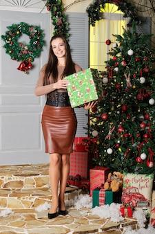 手にクリスマスのギフトボックスと幸せな女性の全身像