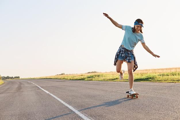 Полный портрет счастливой молодой взрослой женщины, катающейся на скейтборде на открытом воздухе только на асфальтовой дороге, поднятыми руками, в одежде повседневного стиля, выражающей положительные эмоции.