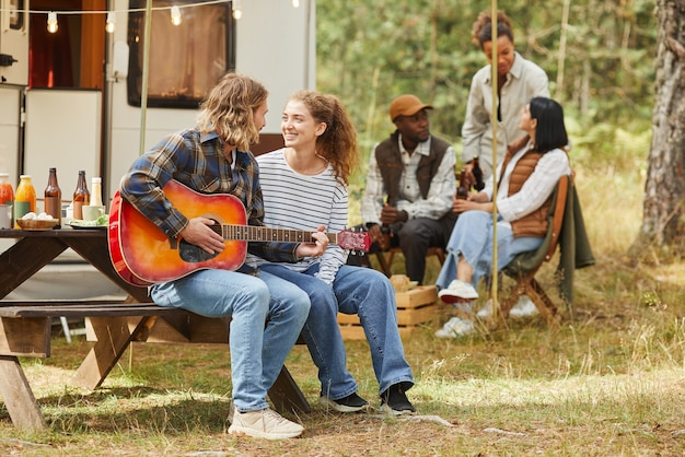 トレイルで屋外キャンプを楽しみながらギターを弾く幸せな若いカップルの完全な長さの肖像画...