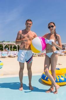 휴가 중 화창한 여름날 카메라에 엄지손가락을 치켜드는 스트라이프 비치 볼을 들고 해변에서 포즈를 취하는 행복한 젊은 커플의 전체 길이 초상화