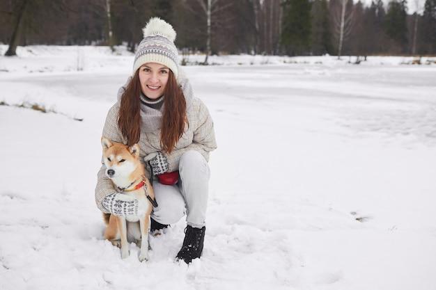 Полный портрет счастливой молодой женщины, позирующей с собакой на открытом воздухе и смотрящей в камеру, наслаждаясь зимней прогулкой вместе, копией пространства
